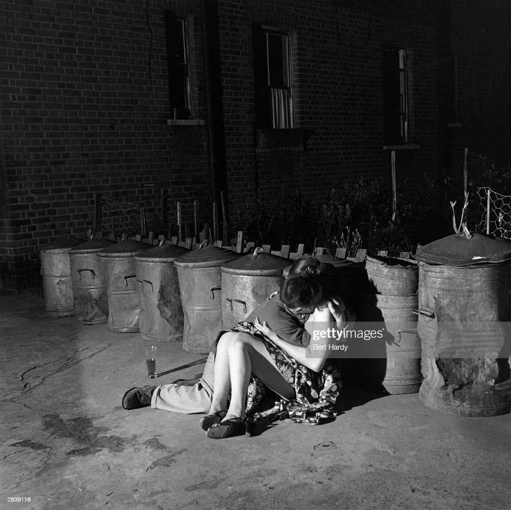 A young couple cuddling in a back yard during an artist's party in Chelsea, London. Original Publication: Picture Post - 5779 - Artists Party - unpub.