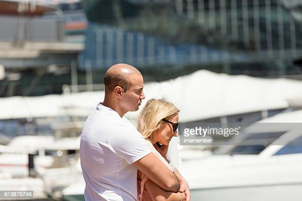 Young couple cuddling in sunshine at Darling Harbour, copy space