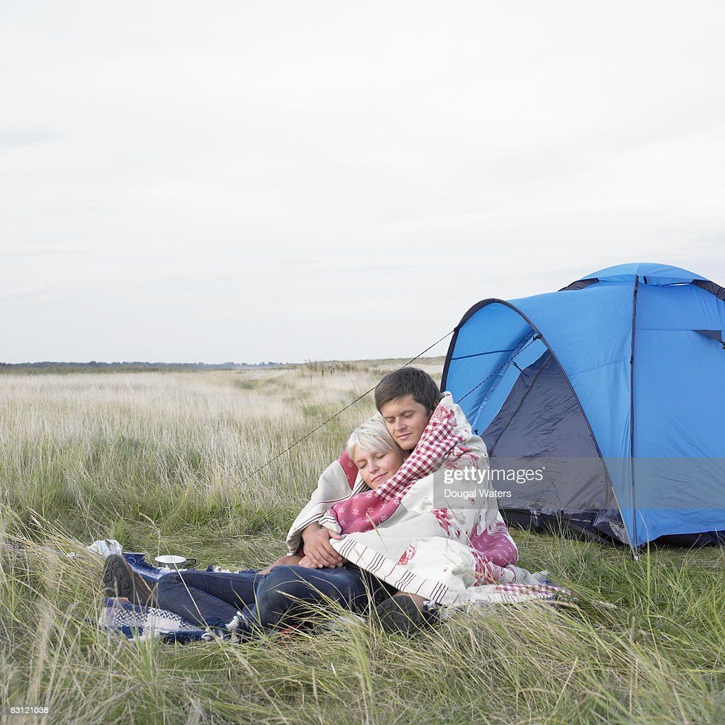 Young Couple Cuddling Under Blanket Next To Tent Stock Photo