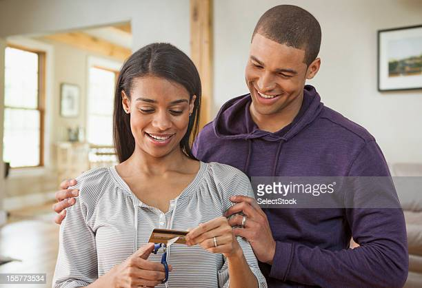 Young couple cutting credit card