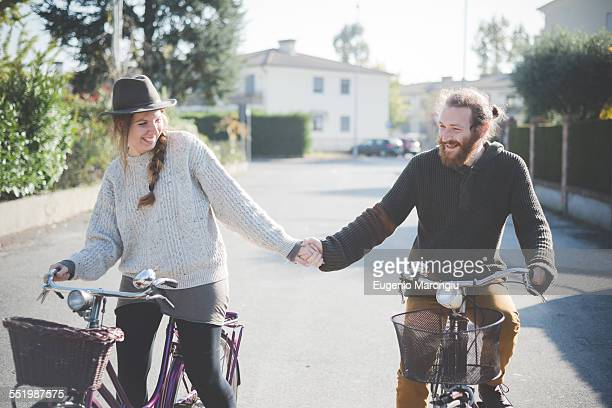 Young couple cycling, holding hands