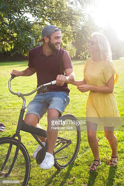 Young couple cycling in sunlit park