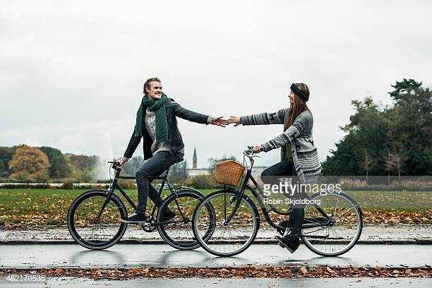 Young couple cycling on street
