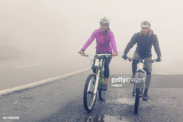 Young Couple Cycling Through The Fog