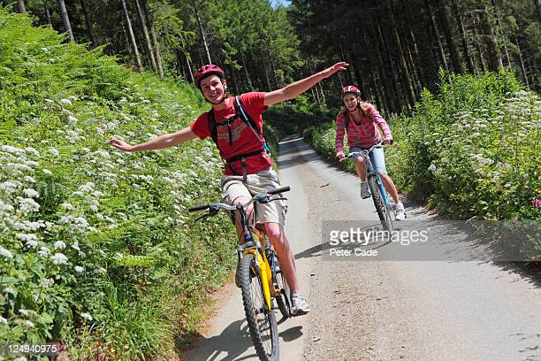 young couple cycling through woods - hands free cycling stock pictures, royalty-free photos & images