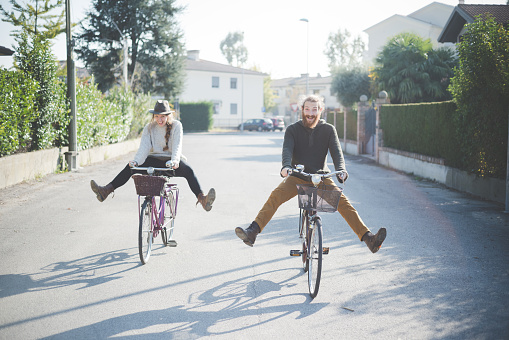 Young couple cycling with legs out - gettyimageskorea