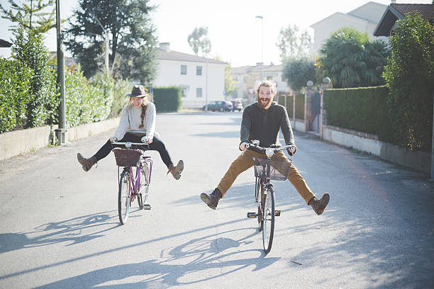 Young Couple Cycling With Legs Out Wall Art