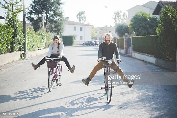 young couple cycling with legs out - insouciance photos et images de collection