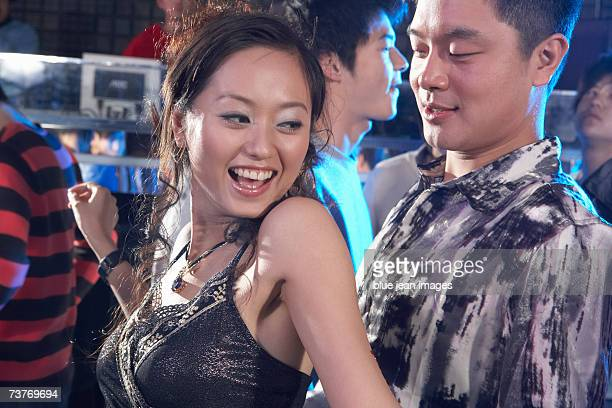 a young couple dance in a nightclub - clubkleding stockfoto's en -beelden