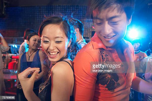 A young couple dance in a nightclub