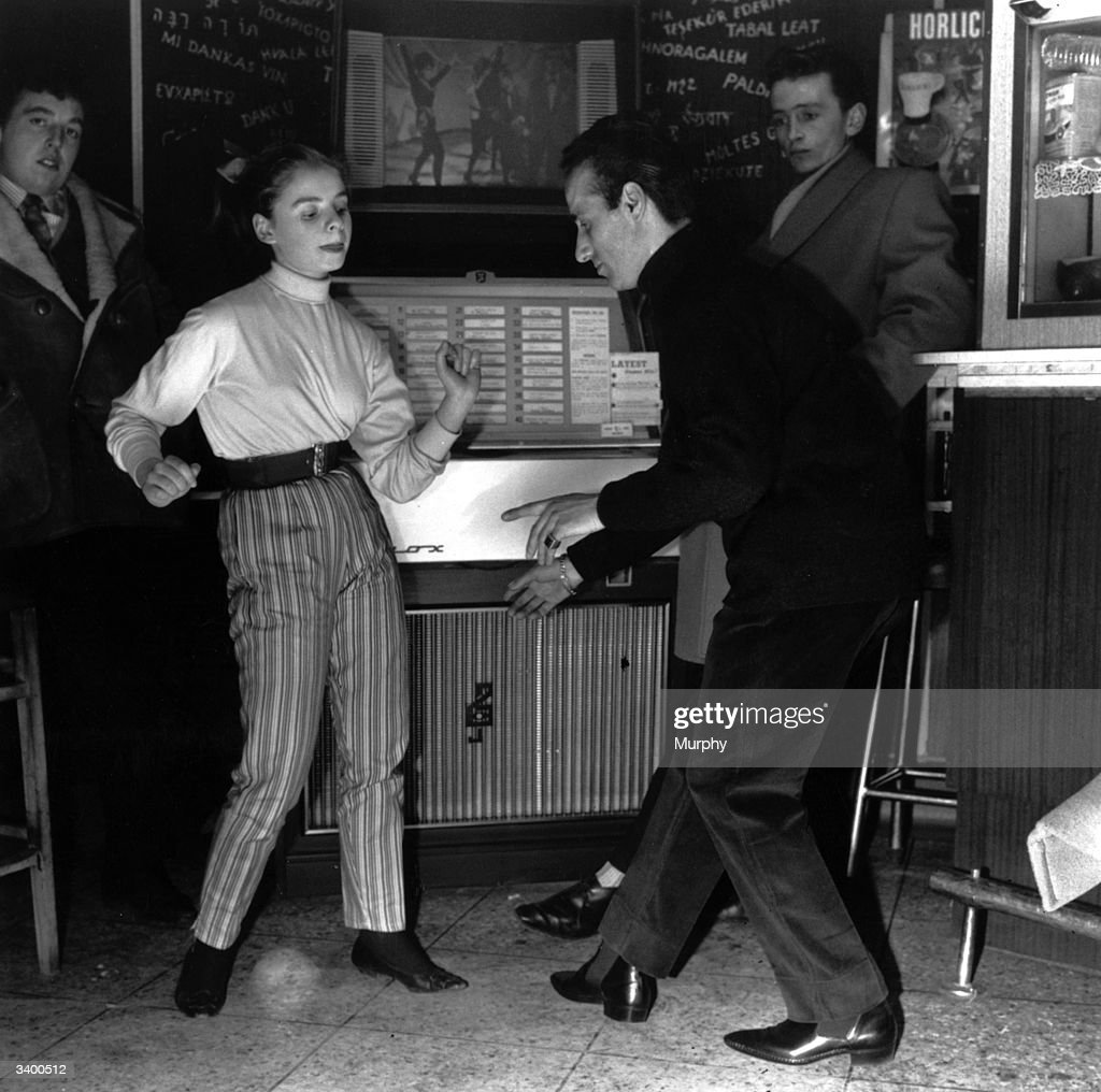 A young couple dance to a jukebox in a coffee bar.