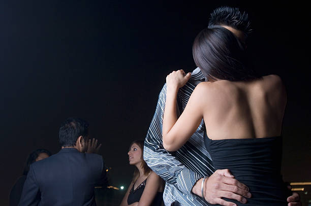 Young couple dancing and kissing at a party