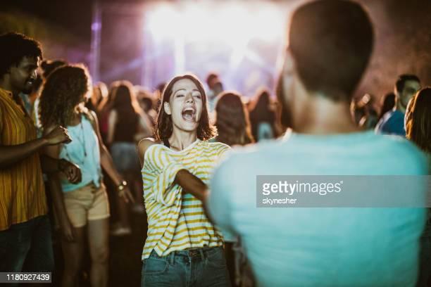 joven pareja bailando y cantando en concierto de música por la noche. - música pop fotografías e imágenes de stock