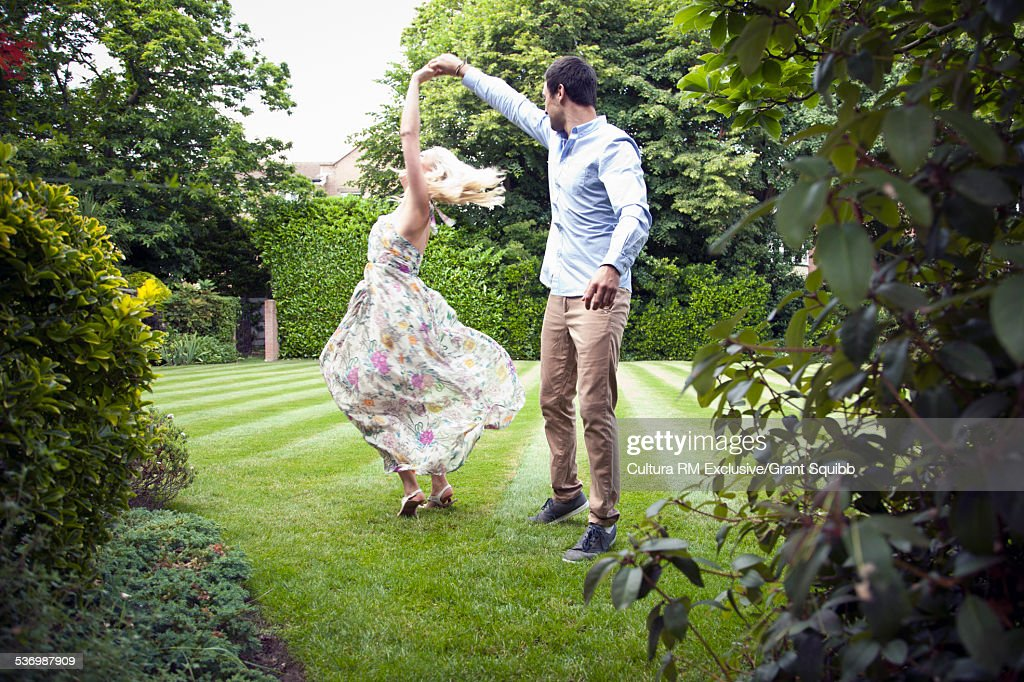Young couple dancing in garden : Stock Photo