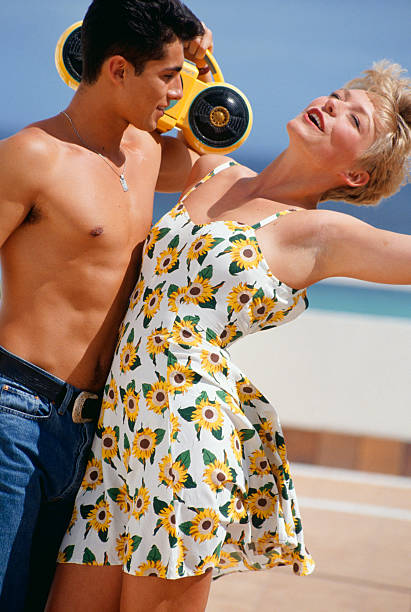 Young couple dancing on beach, listening to stereo