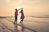 Young couple dancing on beach under sunset.