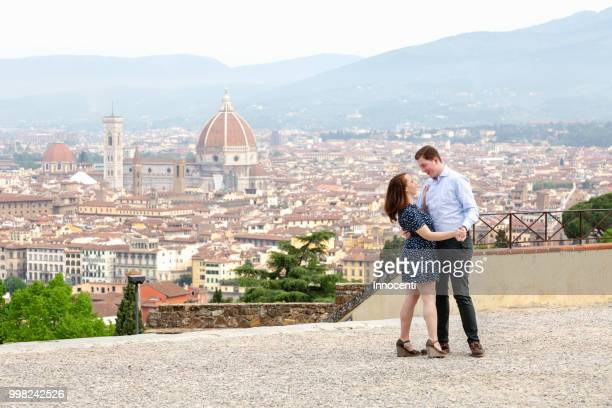 young couple dancing, santa maria del fiore in background, florence, toscana, italy - florence italy ストックフォトと画像