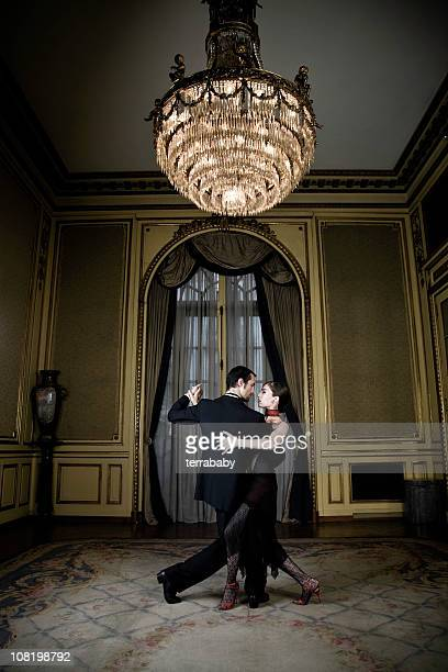 young couple dancing tango in elegant room - balzaal stockfoto's en -beelden