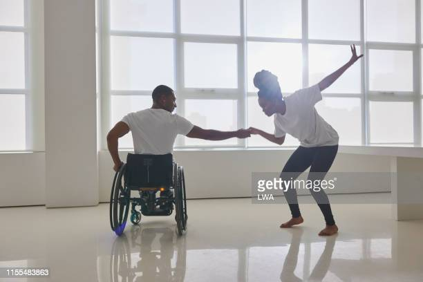young couple dancing together - disabilitycollection stock pictures, royalty-free photos & images
