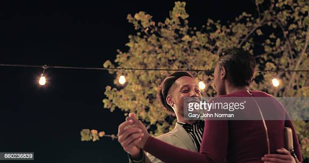 Young couple dancing while out at night.