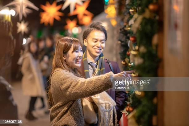 クリスマス マーケットでデートする若いカップル - イルミネーション ストックフォトと画像