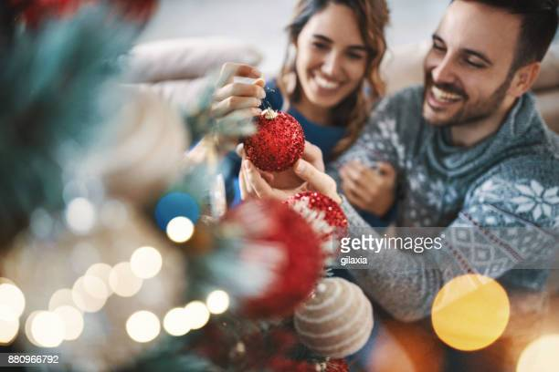 young couple decorating a christmas tree. - ornato foto e immagini stock