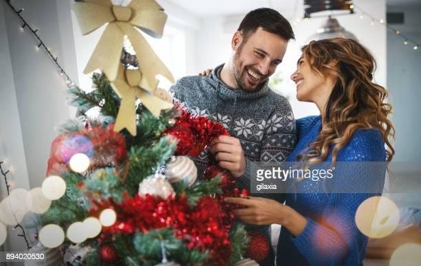 Jeune couple décorer un sapin de Noël.