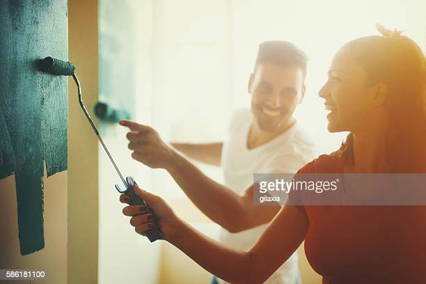 young couple decorating apartment. - dipingere foto e immagini stock