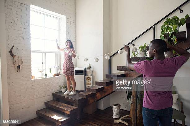 young couple decorating loft with fairylights - decorating stock pictures, royalty-free photos & images