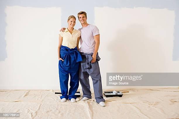 young couple decorating - カバーオール ストックフォトと画像
