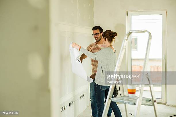 Young couple discussing construction plan