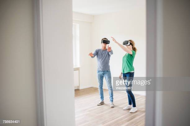 Young couple discussing in empty apartment wearing VR glasses