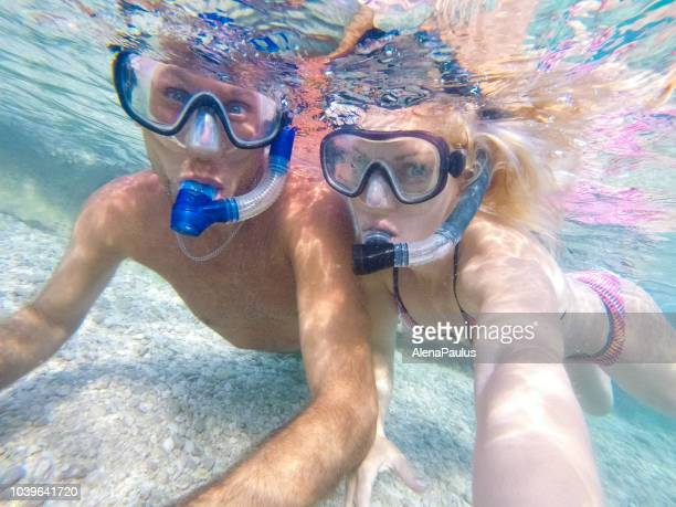 joven pareja buceo bajo el agua - pareja heterosexual fotografías e imágenes de stock