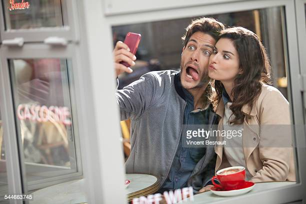 Young couple doing a selfie in a cafe