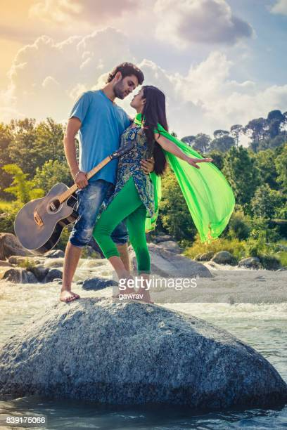 Young couple doing romance on rock in river holding guitar.
