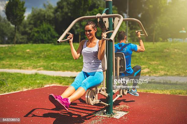 Young couple doing strength exercises on a machine outdoors.