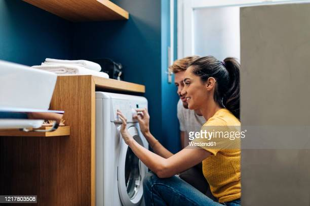 young couple doing the laundry at home - appliance stock pictures, royalty-free photos & images