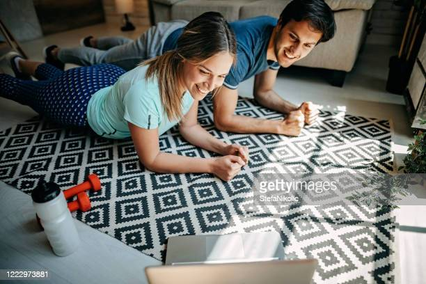 young couple doing workout at home - husband stock pictures, royalty-free photos & images