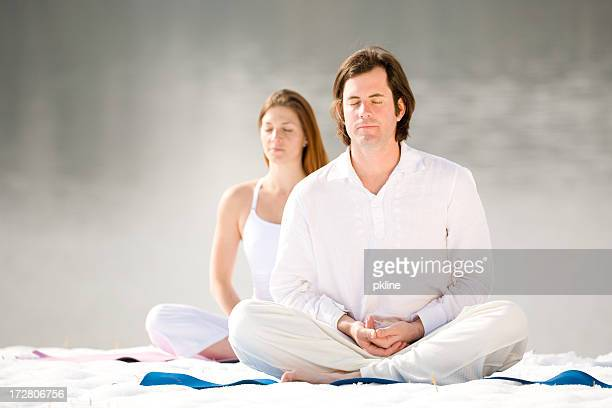 Young Couple doing Yoga in the Snow