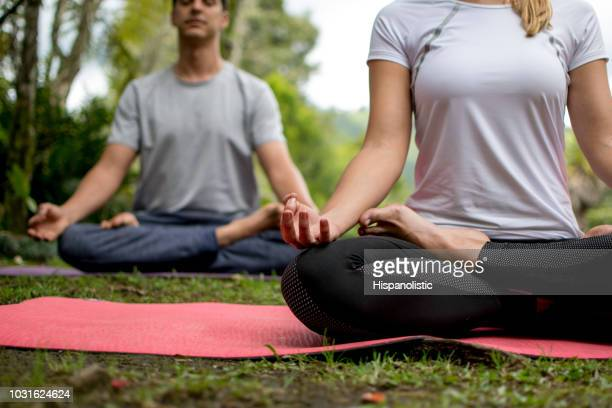 Young couple doing yoga outdoors relaxing doing the lotto pose