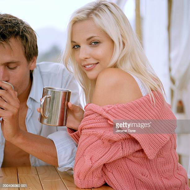 Young couple drinking at table, portrait, side view, close-up