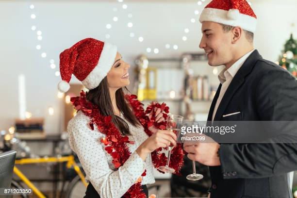 Young couple drinking champagne and celebrating christmas in the office