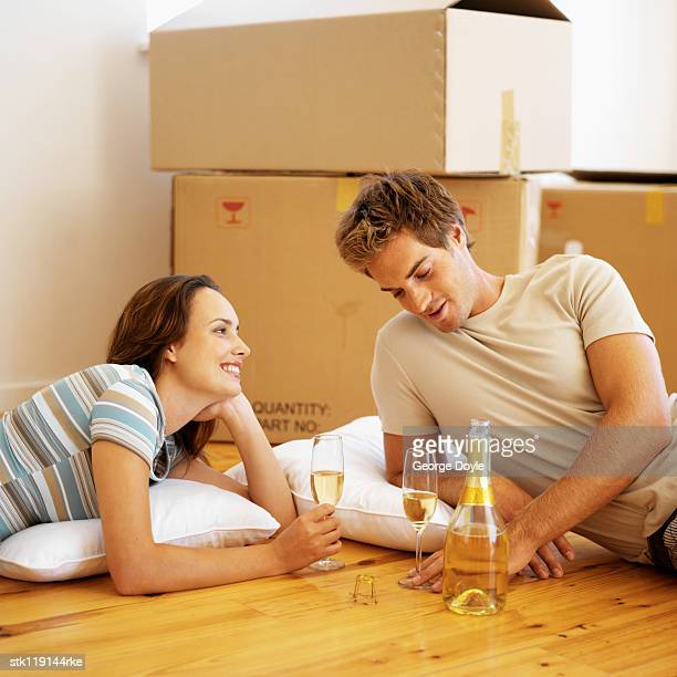 Young couple drinking champagne beside cardboard boxes