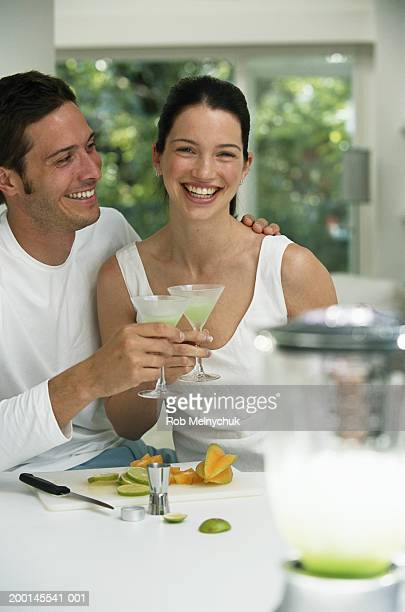 Young couple drinking cocktails in kitchen, portrait