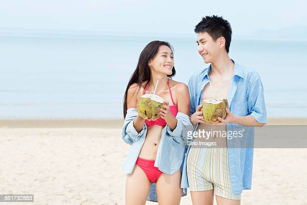 Young Couple Drinking Coconut Juice at the Beach