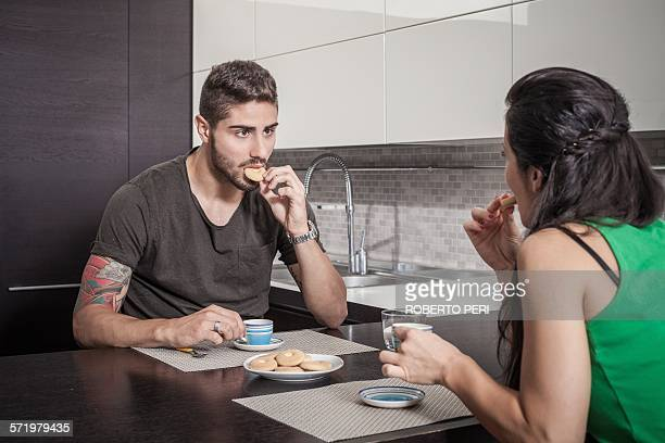 Young couple drinking coffee and eating biscuits at breakfast bar