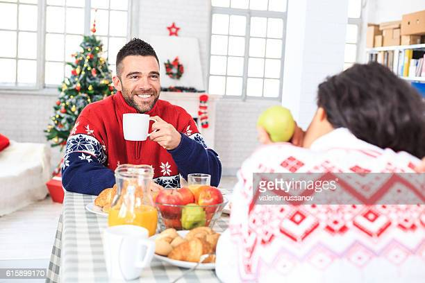 Young couple drinking coffee and having breakfast at home