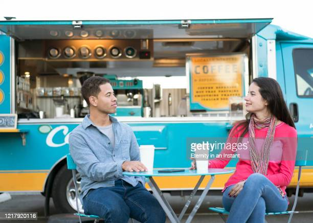 young couple drinking coffee in front of a food truck - オープンカフェ ストックフォトと画像