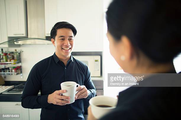 Young couple drinking coffee in the kitchen