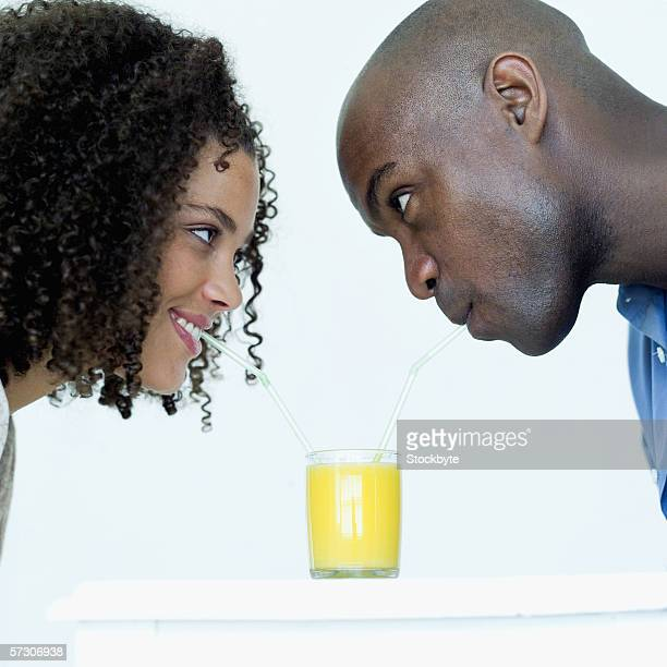 Young couple drinking from a glass using drinking straws